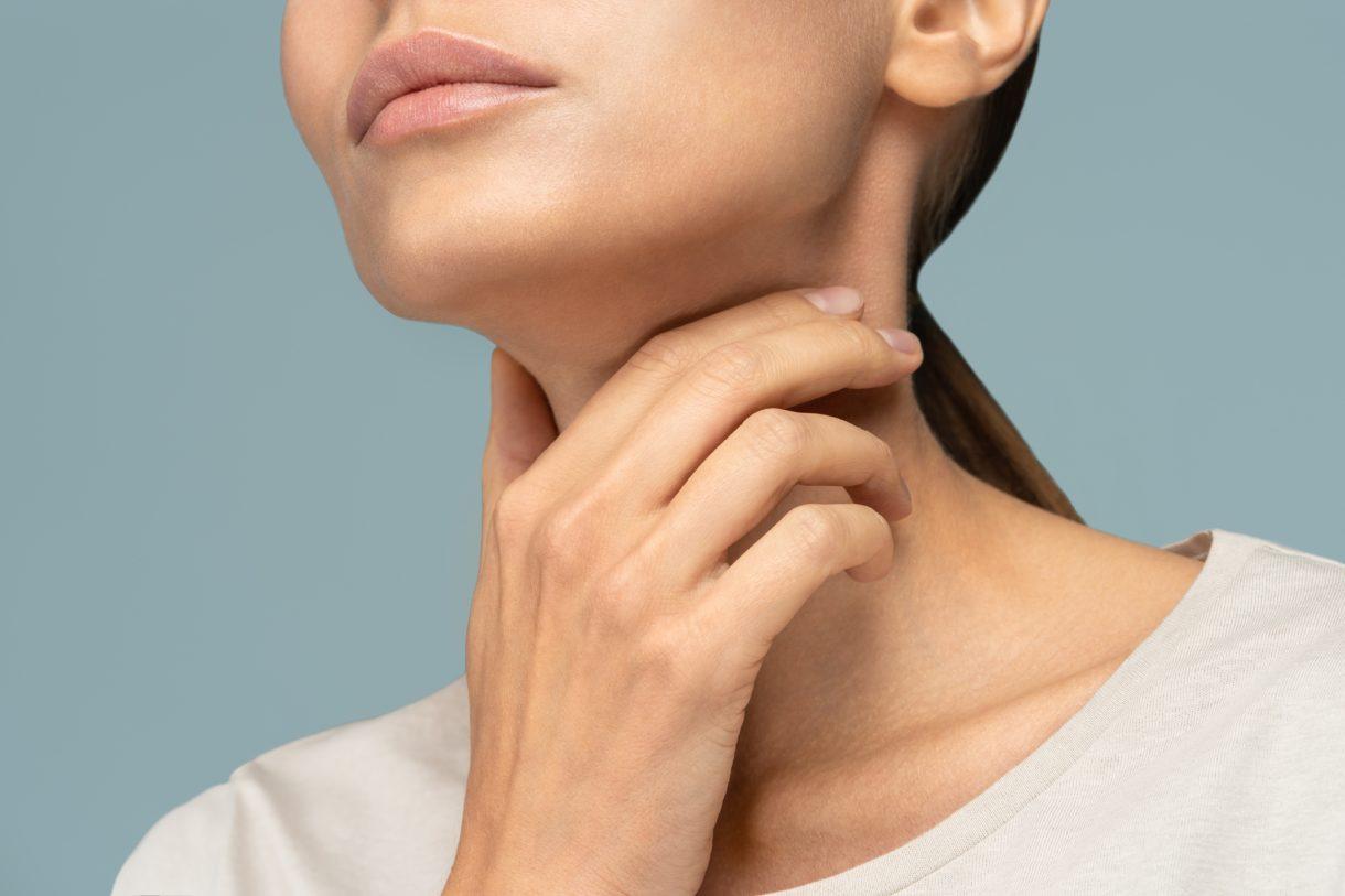 Frau mit Halsschmerzen, Mandelentzündung, leidet unter schmerzhaftem Schlucken, starken Halsschmerzen